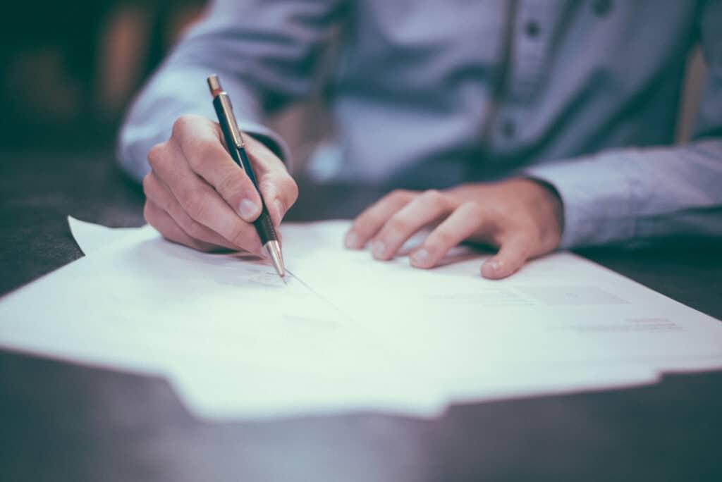 Mann mit Stift und Vertrag