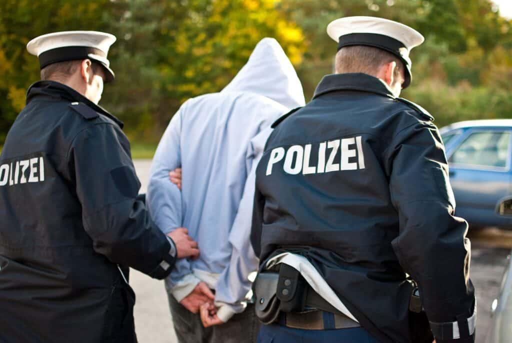 Zwei Polizisten führen Beschuldigten ab