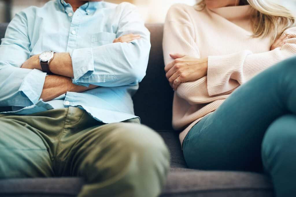 Mann und Frau sitzen mit verschränkten Armen auf Sofa